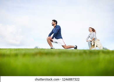 Young active man and woman in sportswear bending knees and stretching legs during outdoor workout