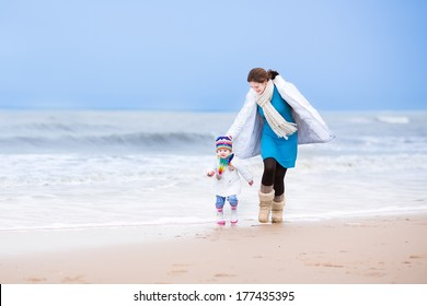 Young active mother and her cute toddler daughter running together on a beautiful windy winter beach in Holland