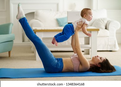 young active mother training at home, doing abs exercise together with her little cute toddler son. fitness, motherhood, parent, sport, healthy lifestyle