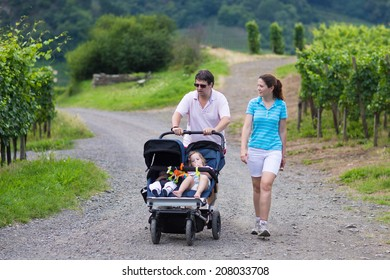 Young active parents hiking in the mountains with a double twin stroller with two children, brother and sister, baby boy and toddler girl