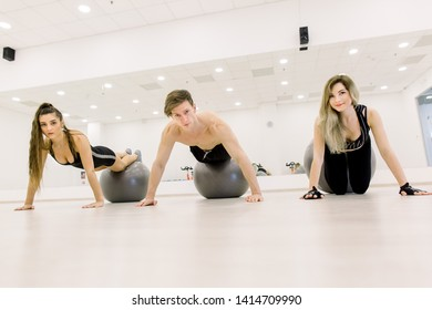 Young active people leaning on the floor by stretched arms with legs on ball during workout in gym.