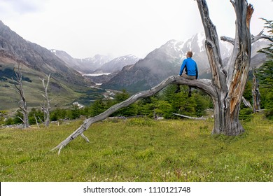 Young active red haired male hiker sitting on a dead tree branch overlooking a misty valley of the Patagonian Andes with mountains, fog and glacier