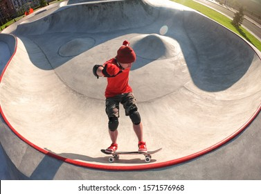 Young active skateboarder riding skateboard in skatepark pool at sunny summer day