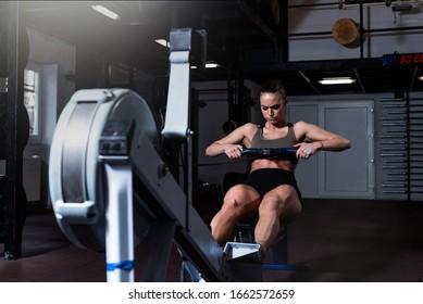 Junge, starke, schwitzige, attraktive Muskelkraft mit großen Muskeln, die harte Kernreihe schwere Kreuztrainings auf Indoor-Rudermaschine im Fitnessraum echte Menschen trainieren