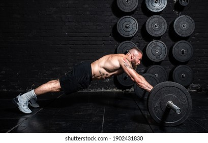Young active strong fit sweaty muscular man with big muscles doing abs workout by rolling barbell weights in the floor of the gym as hardcore training real people exercise