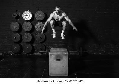 Junge aktive starke schwitzige Muskeln mit großen Muskeln, die Boxspringen trainieren im Fitnessraum als Hardcore-Training realen Menschen trainieren