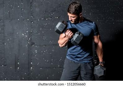 Junge starke muskulöse schwitzige Mann biegt Muskeltraining mit schwerem Hantel Gewicht im Fitnessraum dunkle Bild mit Schatten reale Menschen