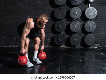 Junge, aktive, starke, schwitzige Muskeln mit großen Muskeln, die Rückenmuskeln trainieren mit Kettlebells im Fitnessraum als Hardcore Cross Training