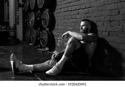 Young active strong sweaty fit muscular man with big muscles sitting on the gym floor and taking a break from hardcore workout cross training real people