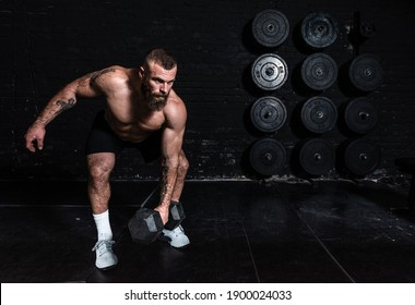 Junge aktive, schwitzige, starke Muskeln mit großen Muskeln, die sich mit Schnaps oder Quetschtrainings mit Hantel Gewicht im Fitnessraum als Hardcore Cross Training