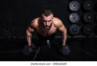 Junge aktive, schwitzige, starke Muskeln mit großen Muskeln, die auf den Hantel im Fitnessraum hochschieben, als Hardcore Cross Training