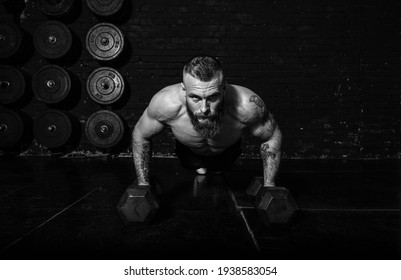 Junge aktive, schwitzige, starke Muskeln mit großen Muskeln, die auf den Hanteln im Fitnessraum, als Hardcore Training realen Menschen trainieren