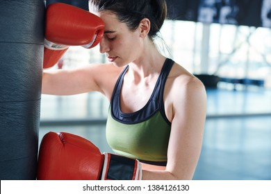 Young active woman in boxing gloves and sportswear having headache or trouble with exercises