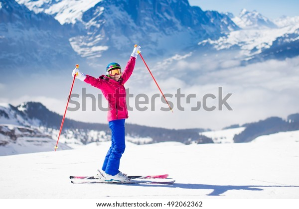 Young active woman skiing in mountains. Female skier kid with safety helmet, goggles and poles enjoying sunny winter day in Swiss Alps. Ski race for adults. Winter and snow sport in alpine resort.