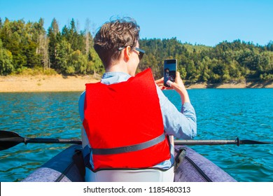 Young active woman taking selfie with smart phone while kayaking on the Lokvarsko lake in Gorski kotar, Croatia. Girl enjoying adventurous experience on a sunny day.