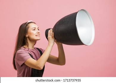 young activist shouts into a megaphone, a young girl in a jumpsuit on a pink background. young girl is shouting into a megaphone, attention please important information