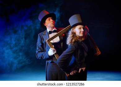young actor and actress in tuxedos and hats dancing