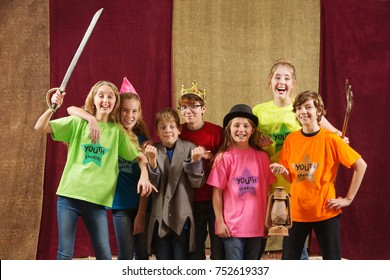 Young actors holding costume pieces smile and pose for the camera