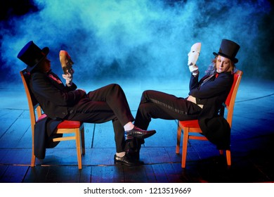 young actors in tuxedos holding theatrical masks