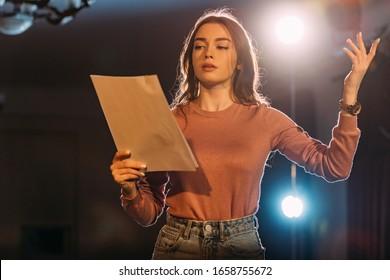 junge Schauspielerin liest Szenario auf der Bühne im Theater