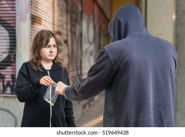 Young addicted woman is buying drugs from drug dealer.