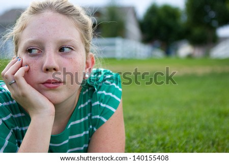 Young adolescent girl looking bored at a park.