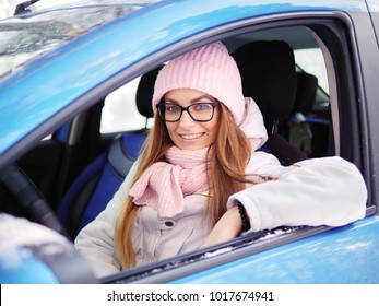 Young adorable blonde woman in pink knitted hat scarf car driver winter outdoors.