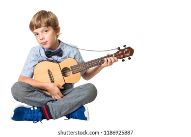 young adorable boy playing the ukulele, isolated on white background with space for text