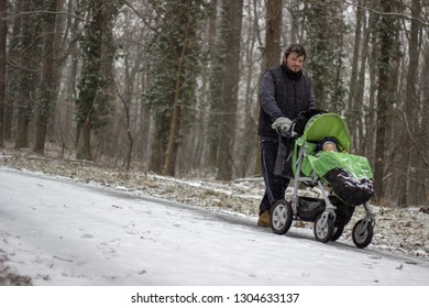 young adorable dad is walking and pushing the stroller with little cute adorable babyboy in it on the path covered with snow in the snowy forest