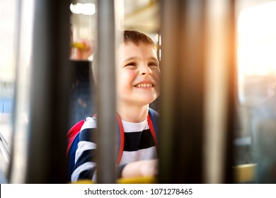 Young adorable happy toddler boy enjoying a ride with the bus. View through the window.