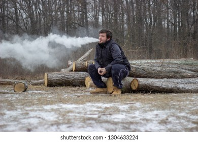 young adorable man sit on wood in forest and exhaling vapor from ecigarette