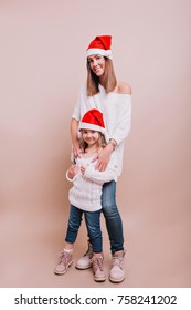 Young adorable mother with little cute daughter are posing to the camera wearing white pullovers and jeans and Christmas hats on the isolated background, Christmas mood, place for text