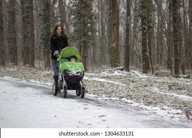 young adorable mother is walking and pushing the green stroller with little cute adorable babyboy in it on the path covered with snow in the snowy forest