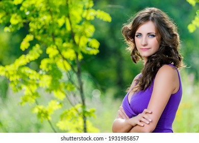 Young adorable smiling woman with long dark curly hair in a purple dress on the background of a summer green city park.