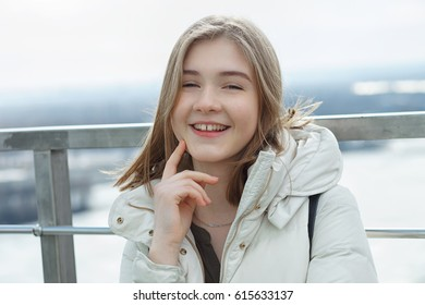 Young adorable student blonde teen girl having fun touching her chin on the observation deck with a view of cloudy spring sky, frozen river, sunny windy weather