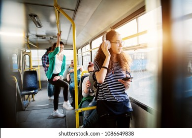 Young adorable woman is adjusting her headset and looking through the bus window while waiting to arrive at her destination.