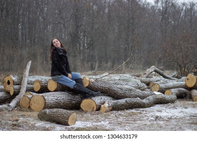 young adorable woman with brown hair is looking aside and sits on the snowy woods with trees in the background