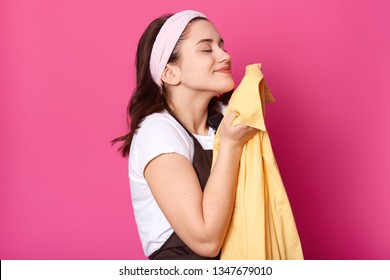 Young adorable woman wears brovn apron and white t shirt, feels satisfied while smells fresh yellow shirt after laundry, isolated over pink background. Copy space for advertisment or promotion text.