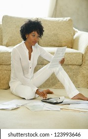 Young adult African American sitting in living room paying bills