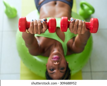 Young adult african american woman in sports clothing at home, doing domestic fitness and training pectorals on swiss ball in living room