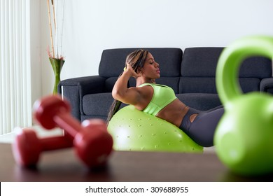 Young adult african american woman in sports clothing at home, doing domestic fitness and training abdominals on swiss ball in living room