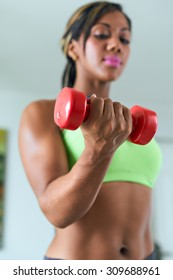 Young adult african american woman in sports clothing at home, doing domestic fitness and training biceps with weight. Focus on weight in foreground