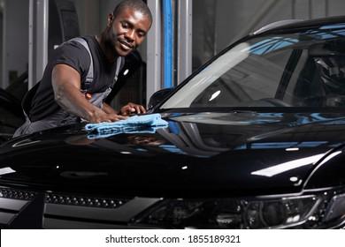 jeune adulte afro-américain homme nettoyant sa voiture avec du tissu en microfibre, un concept de détail ou de validation de voiture