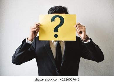 Young adult asian businessman holding yellow signboard paper with QUESTION MARK. Concept of business FAQ and questions