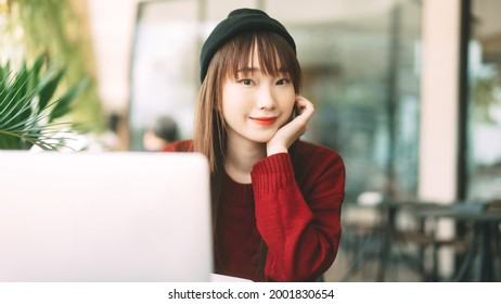 Young adult asian college student woman wear red sweater. Using laptop study and work online at cafe. University people city lifestyle at outside from home on winter day.
