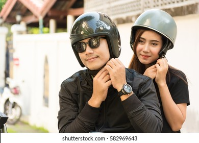Young Adult Asian Couple, Male and Female Biker or Motorcyclist Wearing Safe Helmet before Travel on Motorcycle as Accident Prevention or Safety Riding Concept.