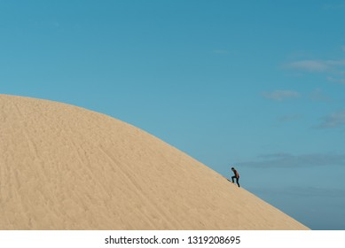 young adult asian male climbing a sand dune against blu sky background. concept of traveler, effort and nature