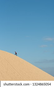 young adult asian male climbing a sand dune against blu sky background. concept of traveler, effort and nature. vertical image