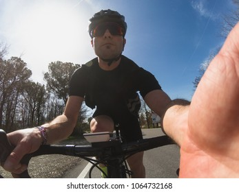 Young adult athlete takes a selfie while training on a racing bicycle in Tuscany on a sunny spring day
