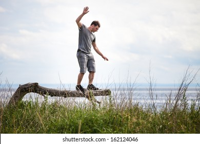 Young Adult Balancing on a dead Tree in Nature.
